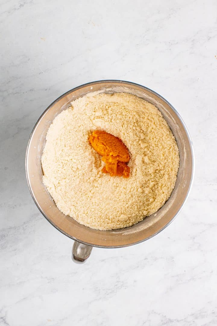 Pumpkin added to flour and butter mixture in bowl of stand mixture.