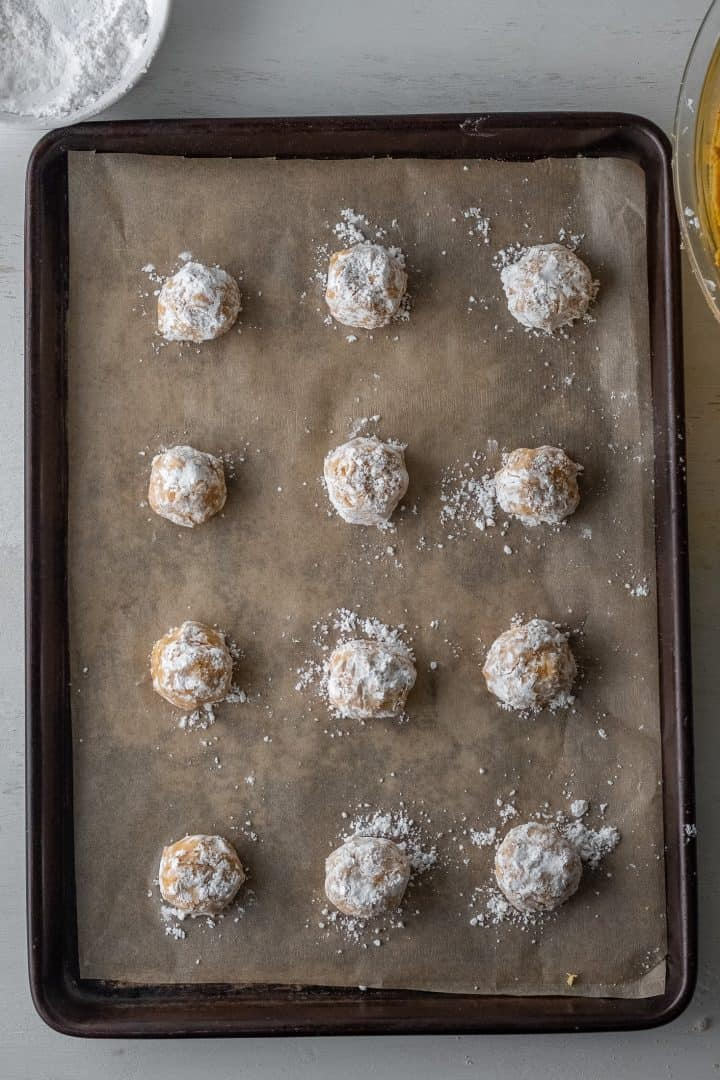 Cookie dough balls added to lined baking sheet.