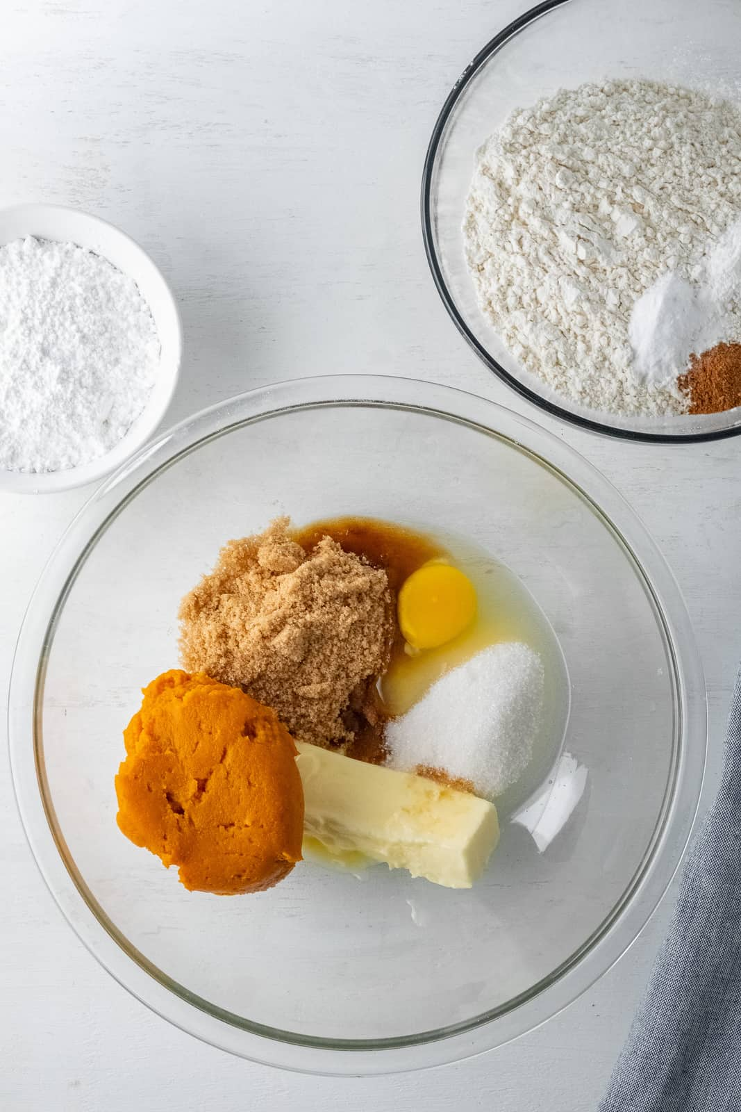Brown sugar, granulated sugar, egg, pumpkin, butter and vanilla added to another clear bowl.