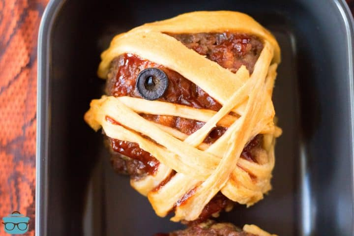 Up close of one Halloween Mummy Meatloaf on black platter showing eye.