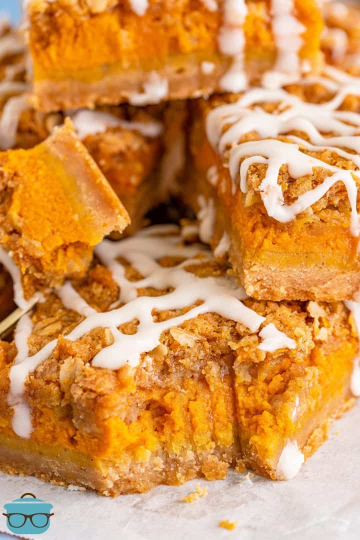 close up photo of pumpkin streusel bars stacked on white parchment paper and a bite removed from one of the bars.
