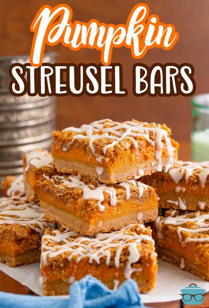 stacked pumpkin bars on a piece of white parchment paper with an old-fashioned flour sifter in the background.