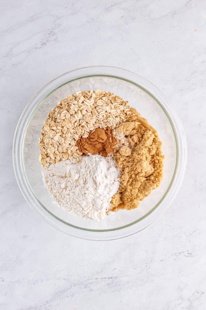 Brown sugar, flour, oats, pumpkin spice, and salt added to clear bowl.