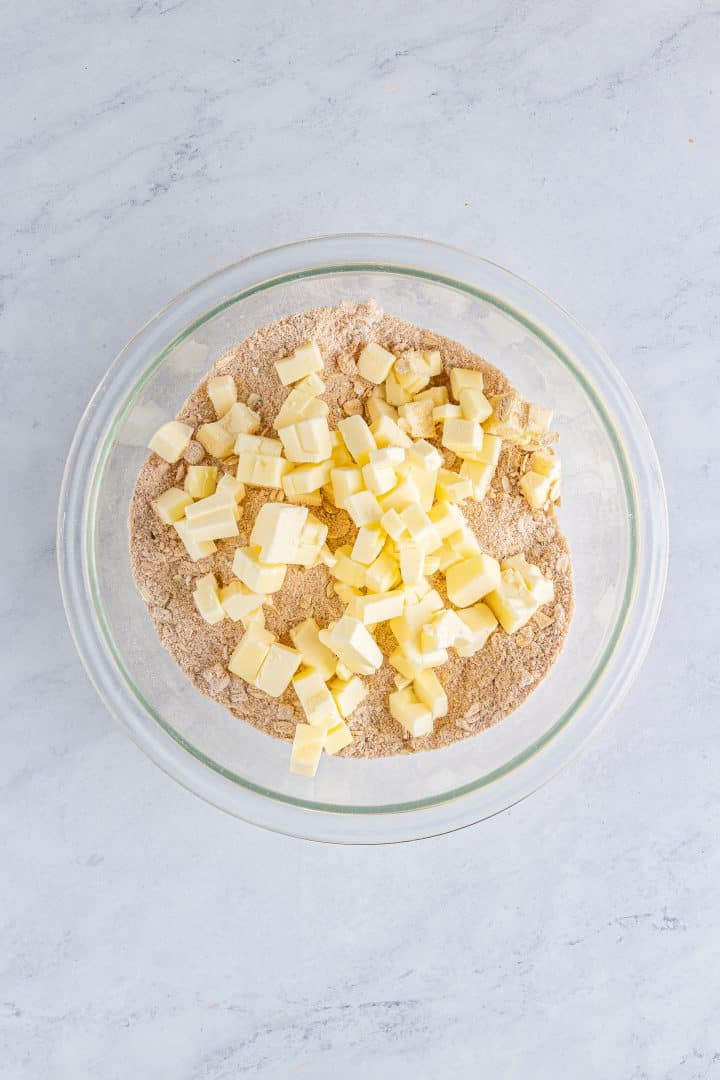 Butter added to brown sugar, flour, oats, pumpkin spice, and salt mixture in clear bowl.