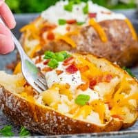 Square image of fork going into finished baked potatoes.