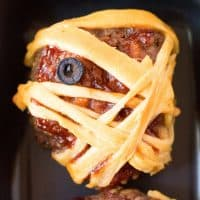 Square image of one baked Halloween Mummy Meatloaf up close on black plate.